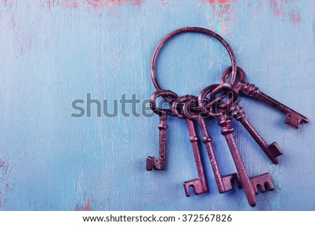 Bunch of old keys on blue wooden background, close up - stock photo