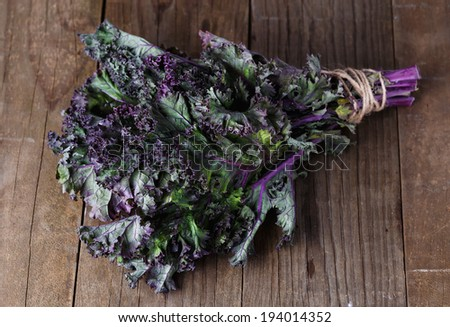 Bunch of organic kale on a rustic wooden background. Selective focus, shallow dof - stock photo