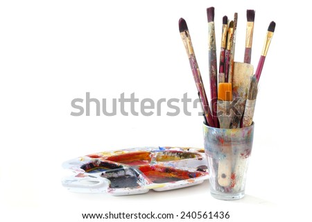 bunch of paint brushes in a glass and a used palette with colors, isolated on white background - stock photo