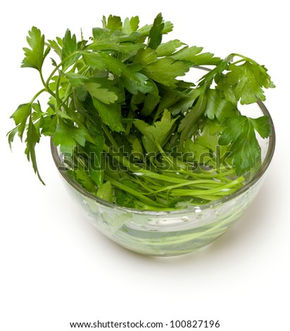 bunch of parsley in a glass bowl isolated on white