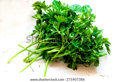 bunch of parsley on a white wooden background and parsley in a colander - stock photo