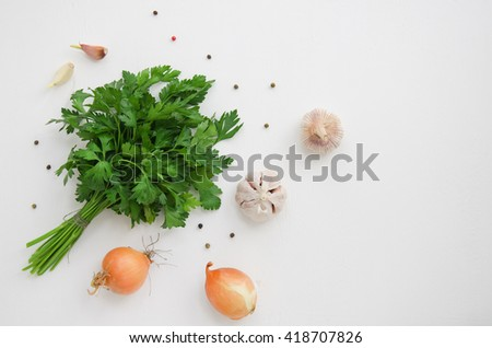 Bunch of parsley, onions and garlic on a white wooden background