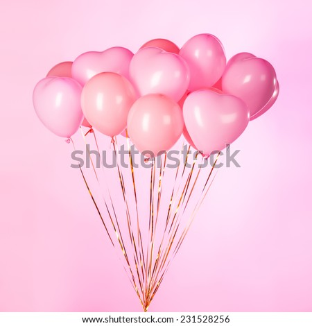 Bunch of pink party balloons on pink background. - stock photo