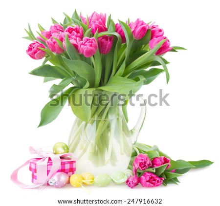 bunch of pink tulip flowers   in glass vase with easter eggs isolated on white background