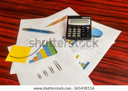 Bunch of printed charts and graphs with calculator, paper clips, yellow note and pen on them