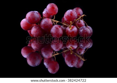 bunch of red grapes isolated on black background - stock photo