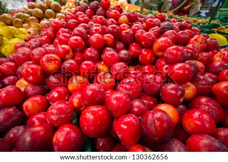 Bunch of red plums in supermarket. Wide angle shot - stock photo