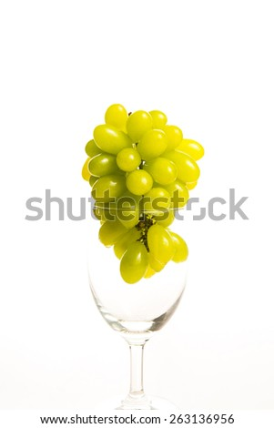 bunch of ripe and juicy green grapes close-up in wine glass on a white background - stock photo