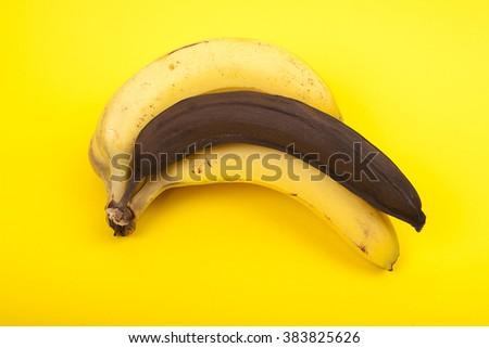 bunch of ripe bananas with one black rotten banana - stock photo