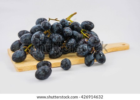 bunch of ripe black grapes with water drops isolated on white background. on  wood - stock photo