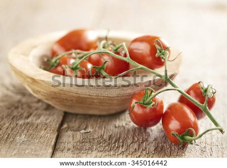 Bunch of ripe fresh mini san Marzano vine tomatoes displayed half in half out of a small wooden dish over a wood background - stock photo