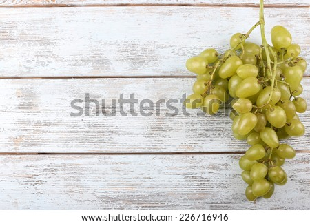 Bunch of ripe grapes on grey wooden background