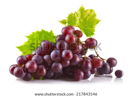 Bunch of ripe red grapes with leaves isolated on white background - stock photo