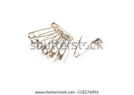 Bunch of safety pins on white background - stock photo