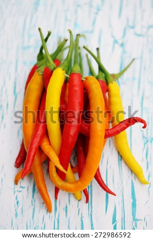 bunch of small chili peppers on a wooden board - stock photo