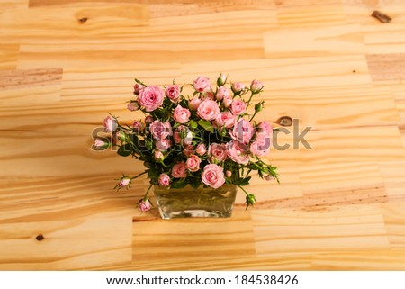 Bunch of small pink Roses in a glass vase over a wooden table.  - stock photo