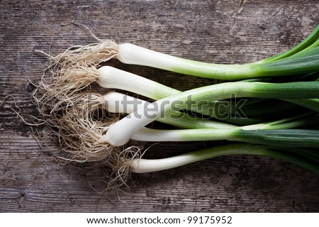 bunch of spring onions on wood - stock photo