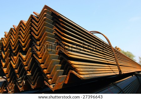 Bunch of steel angles in warehouse against a blue sky - stock photo