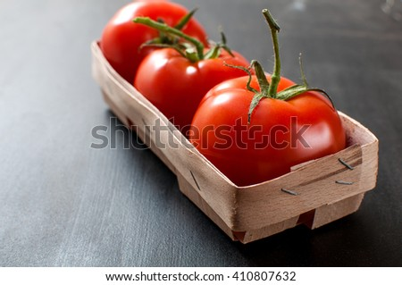 Bunch of three fresh delicious red organic tomatoes in rustic basket on grey old kitchen table, horizontal image - stock photo