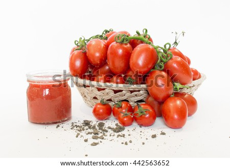 Bunch of tomatoes in a basket with tomato juice
