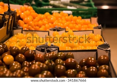 Bunch of tomatoes in boxes in supermarket - stock photo