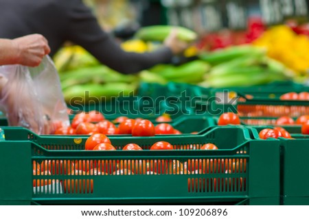 Bunch of tomatoes in plastic boxes in supermarket - stock photo