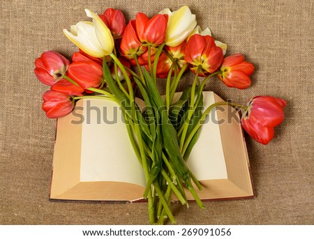 bunch of tulips and an open book on the background of burlap - stock photo
