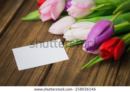 Bunch of tulips and white card on wooden table
