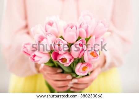 Bunch of tulips in woman's hands, shallow dof. - stock photo