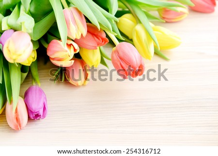 Bunch of tulips on white wooden background - stock photo