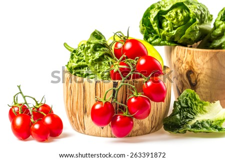 Bunch of vegetables in the wooden bowl. Red tomato, yellow pepper and green salad on white background.