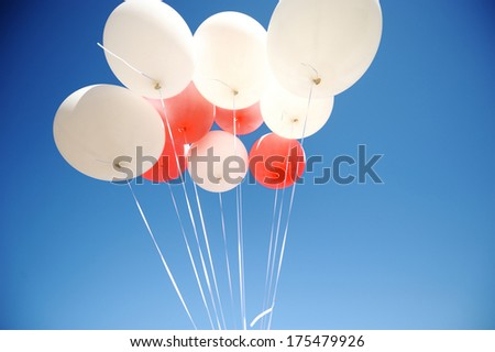 Bunch of white and red balloons in a sky - stock photo
