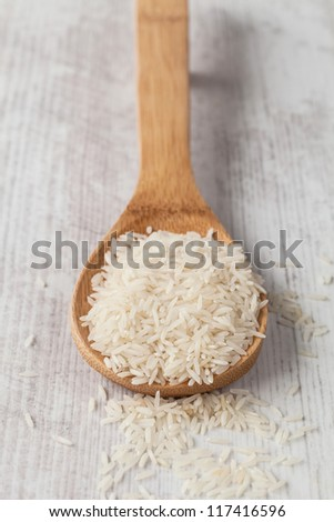 Bunch of white basmati rice on a wooden spoon