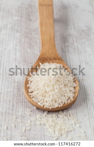 Bunch of white rice on a wooden spoon