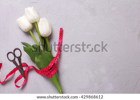 Bunch of white tulips flowers with red ribbon and scissors on grey textured  background. Flat lay with copy space. Selective focus. - stock photo