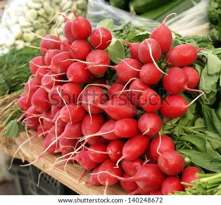 Bunches of fresh radish on market stall - stock photo