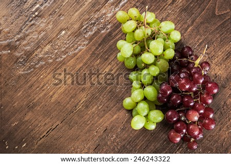 Bunches of fresh washed red and green grapes on a distressed vintage cherry wood table with space for text - stock photo