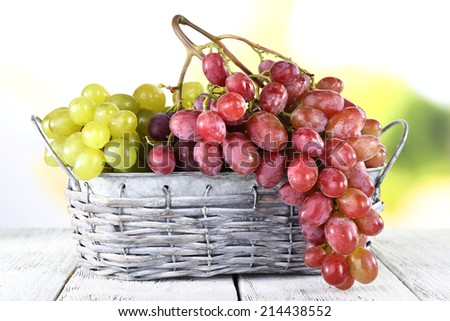 Bunches of ripe grape in wicker basket on wooden table on natural background - stock photo