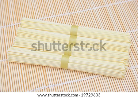 Bunches of spaghetti on bamboo background.