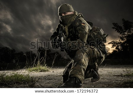 Bundeswehr soldier in a defensive position on the nature background. - stock photo