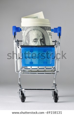 bundle of dollars is watching out of shopping cart - stock photo