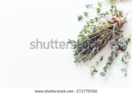 Bundle of raw fresh organic thyme on white wooden table - stock photo