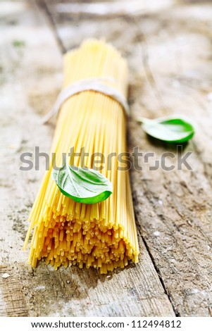 Bundle of uncooked spaghetti with basil for use in the kitchen to prepare fresh Italian pasta dishes - stock photo