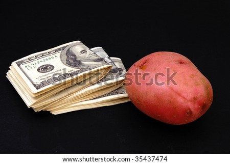 Bundles of hundred-dolar bills and a potato on black background
