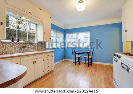 Bungalow kitchen and dining area with blue contrast wall, hardwood floor, kitchen has white cabinets, old-fashioned appliances and mosaic back splash trim. Northwest, USA