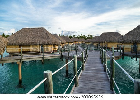 Bungalows over water in tropical dream destinations