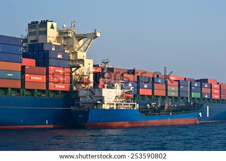 Bunkering tanker Russian Island container ship Hyundai company. Nakhodka Bay. East (Japan) Sea. 19.04.2014 - stock photo