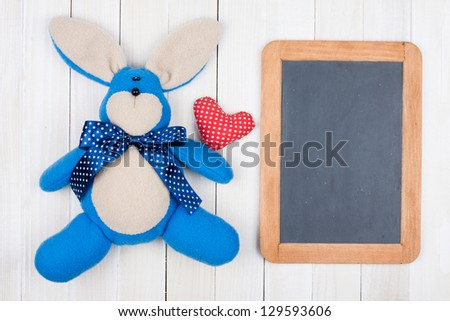 Bunny, heart, blackboard on white wood background - stock photo