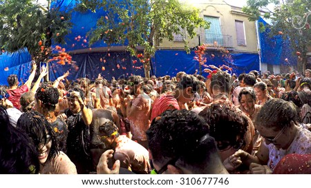 BUNOL, SPAIN - AUGUST 26: La Tomatina festival in August 26, 2015 in Bunol, Spain. Battle of tomatoes at street of city - stock photo