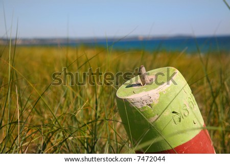 Buoy in the dunes along the beach in Cape cod - stock photo